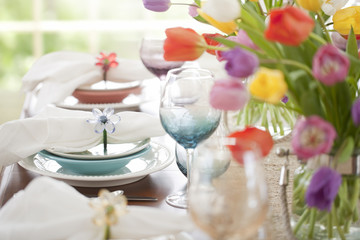 Spring dining table and place setting with a centerpiece of tulips