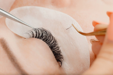 Eyelashes extensions. Eyelash extension procedure in spa beauty salon.