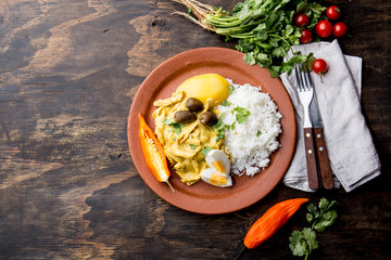 MEXICAN AND PERUVIAN CUISINE. Aji de gallina. Chicken aji de gallina with olives egg and rice on clay plate. Tipical peruvian and mexican dish
