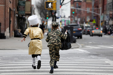 Ultra-Orthodox Jewish boys run across street in costume during the Jewish holiday of Purim in the Williamsburg section of Brooklyn