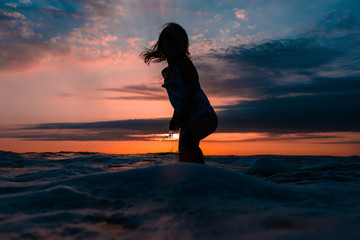 Silhouette Of A Child At A Vibrant Sunset At The Beach