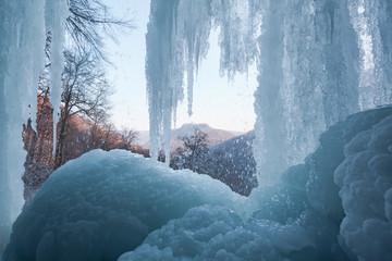 Bad Urach Wasserfall mit Eis und Blick auf die Burgruine Hohenurach.  In der Eishöhle unter den Eiszapfen.