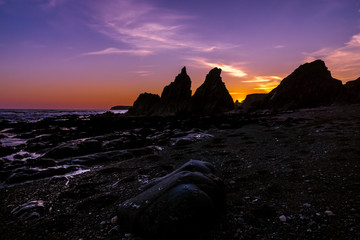 Jagged Rocks Silhouette and Stony Beach Blue Hour