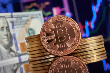 Gold coin bitcoin stacked on a bright background of business graphics close-up. Bitcoin crypto-currency. Virtual currency
