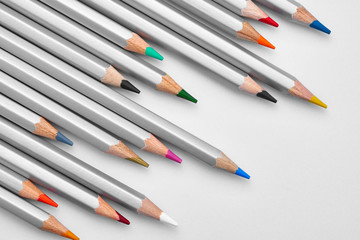 Texture of the school supplies on the blackboard close-up. Bright colorful pencils on a white background lined diagonally. Ready background for design