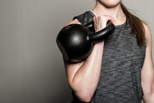 Woman working out in the home gym with kettle bell