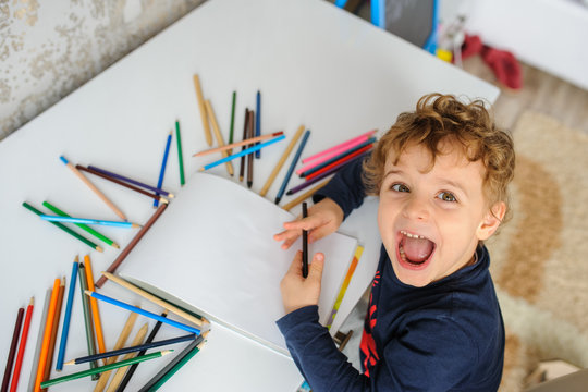 little boy paints greeting card with colour pencils and smile