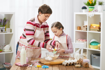 mother and daughter mother and daughter break egg into flour, home kitchen interior, healthy food concept