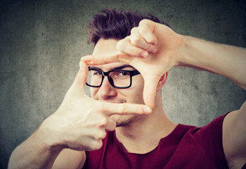 Photographer framing hands looking at camera
