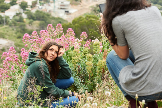 Girl taking photo of her friend in wild pink flowers.