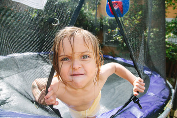 Little boy peering out of trampoline net screen with cute mad expression