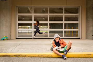 Boy in hood reads while his sister leaps behind him waiting for school doors to open
