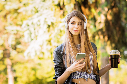 Teenage girl in park with smart phone and coffee listening to music on headphones