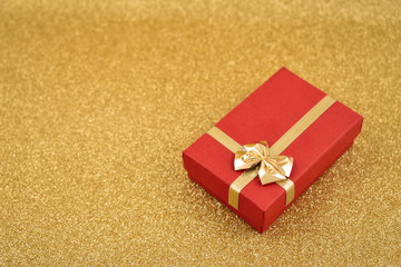 Red gift box stock images. Red gift box with golden bow. Red gift box on a golden background. Golden holiday background with gift. Golden festive background with copy space for text