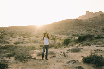 sexy woman in cowgirl look standing in the desert at sunset