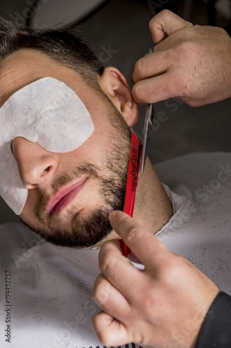 hairdresser shaving his beard with scissors to a client. Black Bedroom Furniture Sets. Home Design Ideas