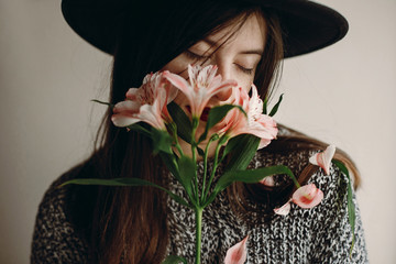 stylish hipster girl in hat holding pink flowers and petals on sweater growing. boho woman with beautiful alstroemeria in hands, smelling flower. creative sensual female portrait. eco concept