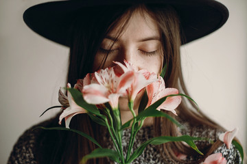 stylish hipster girl in hat holding pink flowers and petals on sweater growing. boho woman with beautiful alstroemeria in hands, smelling flower. creative sensual female portrait. calm face
