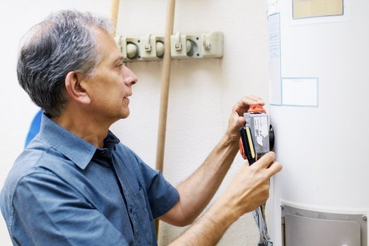 Man checking water heater at vacational rental