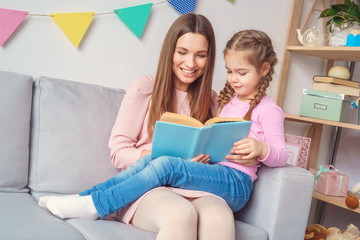 Mother and daughter together at home reading book
