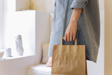 Closeup of Woman's Hand Holding Paper Shopping Bag