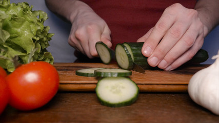 Kitchen table with vegetables, cucumber, tomato, green salad, garlic and knife.