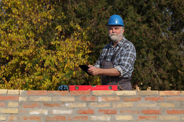 Worker or engineer control brick wall using level tool and tablet, real people, no retouch