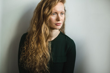 Simple portrait of a red headed woman sitting looking at camera
