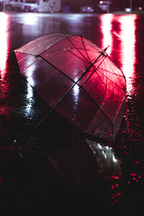 umbrella in wet streets with city lights red