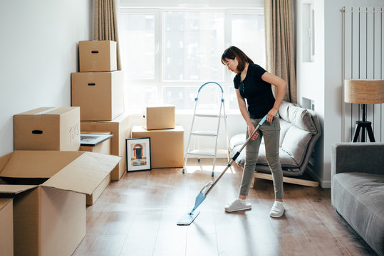 Young  woman cleaning at new home