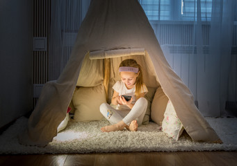 Little girl with smartphone sitting in teepee tent