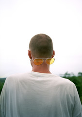Young man with shaved head and yellow sunglasses