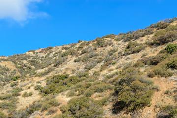 Climbing up the ridge to blue sky on hiking trail