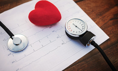 Doctor workplace. Stethoscope with cardiogram on the wooden table. Medical concept