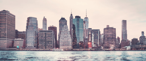 Retro stylized panoramic picture of the Manhattan skyline at sunset, New York City, USA.