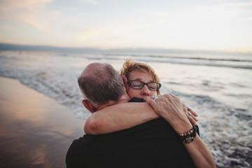 Loving middle aged woman hugging partner outside on ocean beach