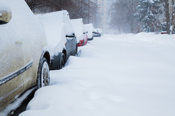Row of cars covered with snow. Snowstorm