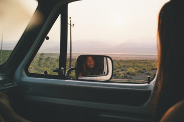A woman looks out into the desert with her reflection the the car mirror.