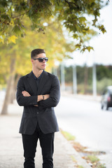 Good looking man in fashion shoot, wear black dress shirt and sunglasses standing on the street with crossed hands