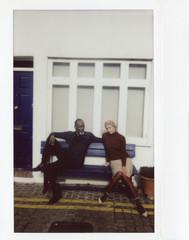 Stylish couple sitting on bench.