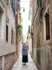 Woman looking up on narrow street