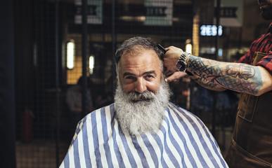 Bearded man getting hair cut