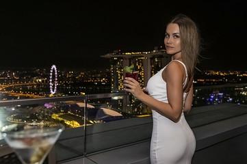 красивая молодая женщина в белом платье с глубоким декольте и большой грудью сидит в баре на крыше на фоне огней ночного сингапур
