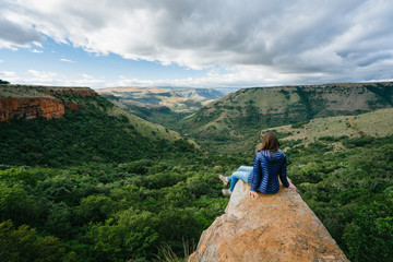 Hiker sitting on a rock outcrop overlooking a scenic mountain valley