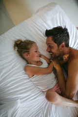 Energetic dad playing with kids in hotel room