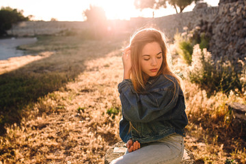 Young thoughtful woman with sunlight behind