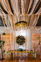 A venue set up for a wedding reception with copper and green colored decor.