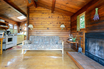 Cozy interior of a rustic log cabin with a kitchen and fireplace.