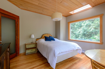 Bright bedroom with great forest view in a rustic cottage. Home interior.