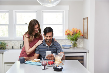 Young couple having breakfast together at home in the morning while looking at mobile phone